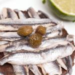 Pumpernickel-Canape mit kleinen Sardinen